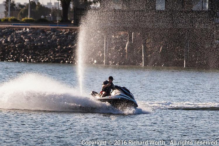 Water spray fills the air behind a personal watercraft, commonly called a Jet Ski, at San Leandro Marina Park along San Francisco Bay, California.