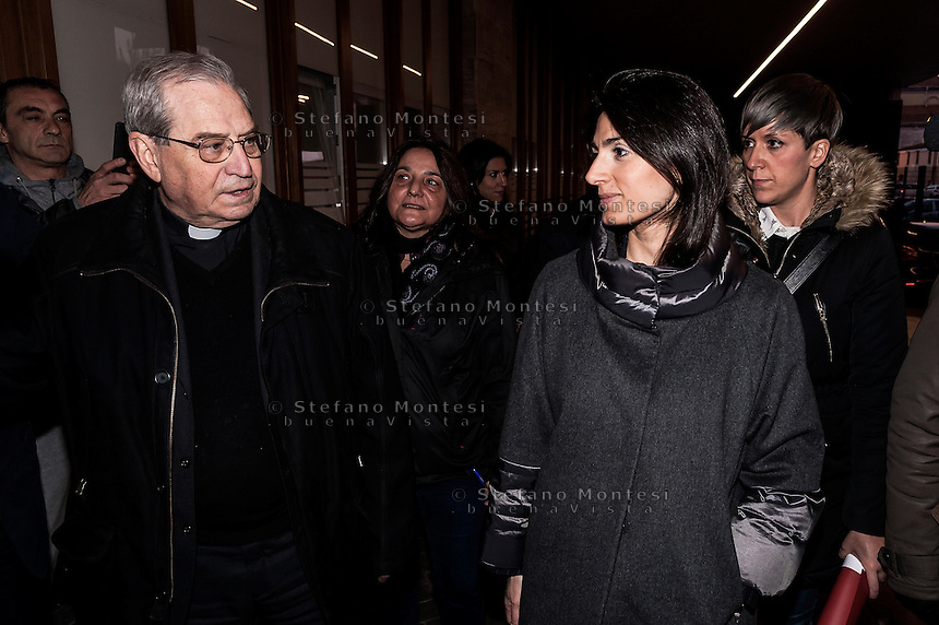 "ROME, ITALY -  DECEMBER 24:   Mons. Enrico Feroci (L), director of Caritas in Rome and Rome Mayor Virgina Raggi  during  Christmas Mass at the hostel ""Don Luigi Di Liegro"" to Termini Station, with the  guests of Caritas on December 24, 2016 in Rome, Italy. (Photo by Stefano Montesi/Corbis via Getty Images)"