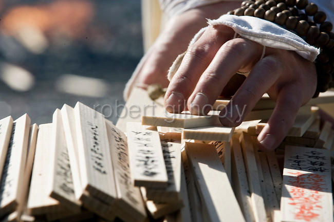 """A priest from the Shingo sect  of Buddhism collects wooden prayer tablets known as """"nadegi"""" to throw on the flames of a fire used in a purification ritual at Mt. Takao near Tokyo, Japan on March 14 2010."""