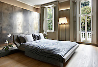 A contemporary bedroom has been created in a Victorian-era apartment block, which retains the original windows and cornicing. Light reflects off a large metallic cabinet installed behind a king size bed.