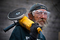 Welder poses for portrait holding grinder used to cut steel for an awning installation at a restaurant.
