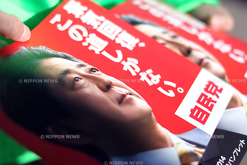 A staff distributes manifestos bearing a photograph of Japan's Prime Minister Shinzo Abe, leader of the ruling Liberal Democratic Party (LDP), during a campaign for the Dec. 14 lower house election, in Toyosu, a man-made island in Tokyo, Japan on Sunday, December 7, 2014. (Photo by Yuriko Nakao/AFLO)