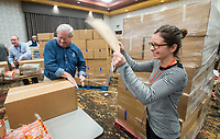 NWA Democrat-Gazette/BEN GOFF @NWABENGOFF<br /> Edith Drew, a Tyson employee from Chicago, walks around fanning her colleagues as they fill meal boxes Wednesday, Dec. 5, 2018, at Embassy Suites Northwest Arkansas in Rogers. More than 800 Tyson employees from across the country who are in town this week attending the company's annual sales conference took the afternoon to pack and load food donations. The employees helped distribute 35,000 pounds of Tyson products to Northwest Arkansas organizations with feeding services and food banks. In addition 1,000 meal boxes, 15,000 snack packs and personal hygiene kits were packaged and distributed to Northwest Arkansas non-proffits.