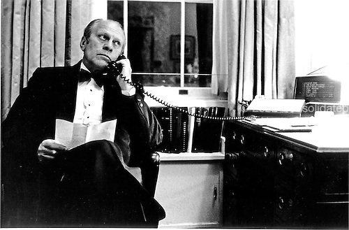 United States President Gerald R. Ford speaks by phone with United States Secretary of State Henry A. Kissinger for an update on the Mayaguez Incident at the White House in Washington, D.C. on May 14, 1975.  Ford was hosting a black tie dinner for the Prime Minister of the Netherlands.<br /> Mandatory Credit: David Hume Kennerly / White House via CNP