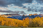 Uncompahgre National Forest, Colorado: Cliffs of the Cimarron stand above fall colored hillsides in evening with sunset light, San Juan Mountains