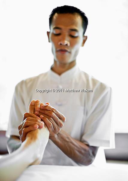 Balinese male spa therapist giving foot Refloxology Massage at Ayung Spa, Ubud Hanging Gardens, Bali, Indonesia.
