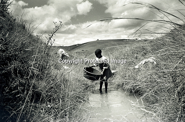 disiabu00055.Social Isuues. Abuse. Bawinile Zulu, age 11, washing clothes with her mother in a stream close to their house in Nqabeni, a rural area outside Port Shepstone, in Southern Natal Province, South Africa. Bawinilie was raped by a neighborÕs son a couple of weeks earlier. In this very traditional Zulu area, most things are solved through negotiation and compensation. The girlÕs father was compensated with two cows for the breaking of the virginity. Bawinilie will start another school, as the father believes that she might get teased in the nearby school. The 22-year old suspect is arrested and is awaiting trial on February 2, 2002 in Port Shepstone, South Africa..©Per-Anders Pettersson/iAfrika Photos