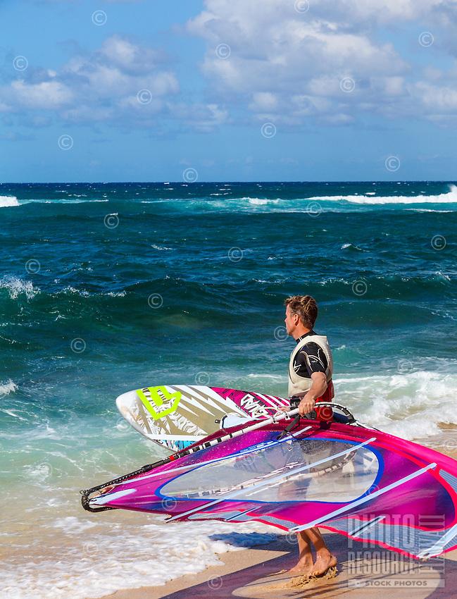 A windsurfer looking out at the ocean at Ho'okipa Beach, Maui.