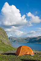Orange single person tent camping above lake Bygdin in rugged terrain of Jotunheimen national park, Norway