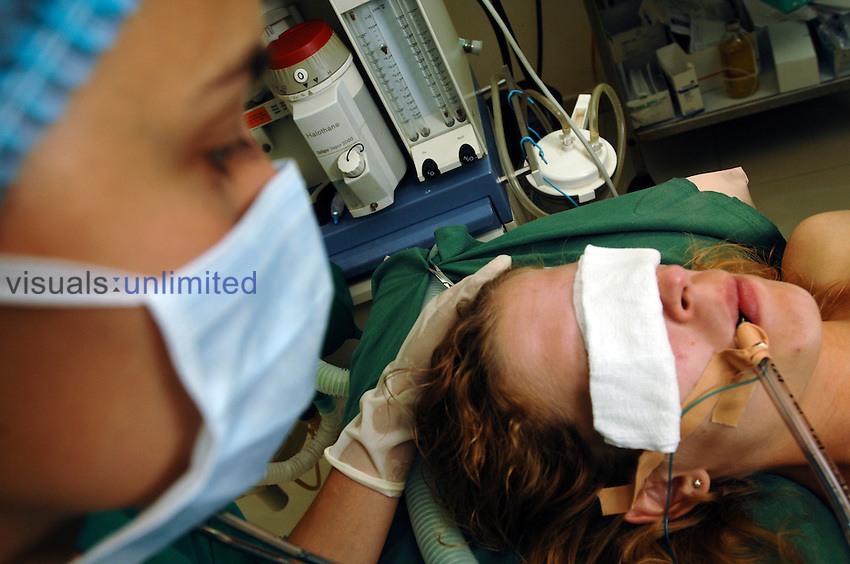 A female patient with her eyes covered at the start of a tracheotomy operation. As a surgeon is about to make an incision in her neck with a scalpel she breathes through an endotracheal (ET) tube which has been hooked to a mechanical ventilator.
