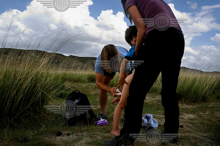"""Rowan, a five-year-old autistic child, is cleaned by his parents after soiling his pants during a horseback expedition across Mongolia. Rowan, who has been nicknamed """"The Horse Boy"""", embarked on a therapeutic journey of discovery with his parents to visit a succession of shaman healers in one of the most remote regions in the world. Following Rowan's positive response to a neighbour's horse, Betsy, and some reaction to treatment by healers, Rowan's parents hoped that the Mongolian shamanistic rituals along the route and the prolonged contact with horses would help to unlock their son's autism and assist his development.."""