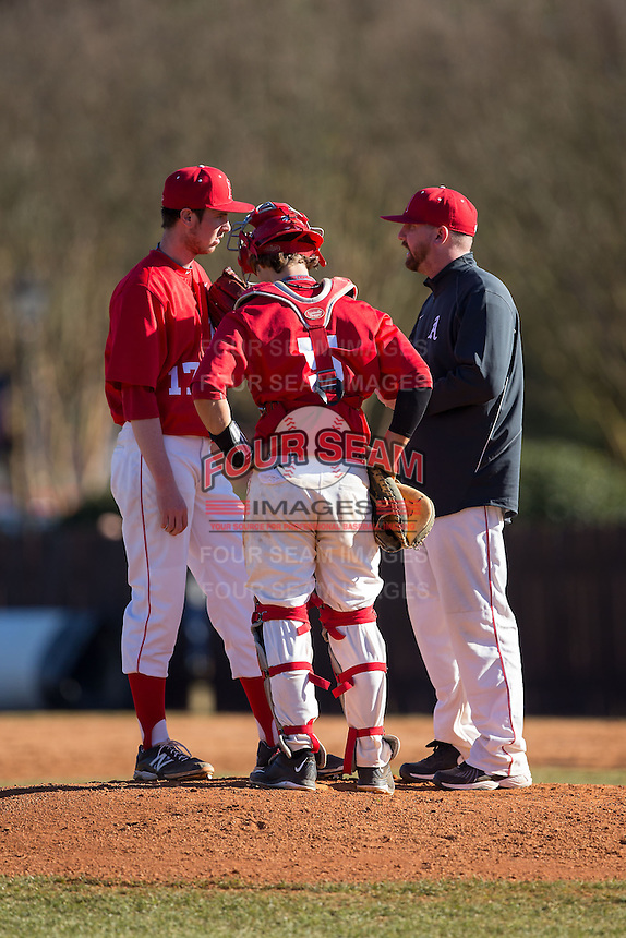 Belmont Abbey Crusaders head coach Chris Anderson (left) has a meeting on the mound with relief pitcher Stephen Hueber (17) and catcher Drew Sipp (5) during the game against the Shippensburg Raiders at Abbey Yard on February 8, 2015 in Belmont, North Carolina.  The Raiders defeated the Crusaders 14-0.  (Brian Westerholt/Four Seam Images)