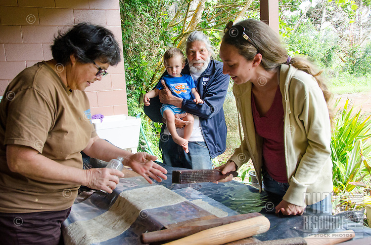 A woman (right) and her family learn how to make kapa or tapa with Roen Hufford, Big Island.