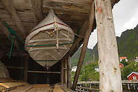 small wooden rowboat hanging under building, Å, Lofoten islands, Norway