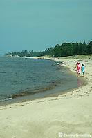 Young girls running along the sandy lake shore