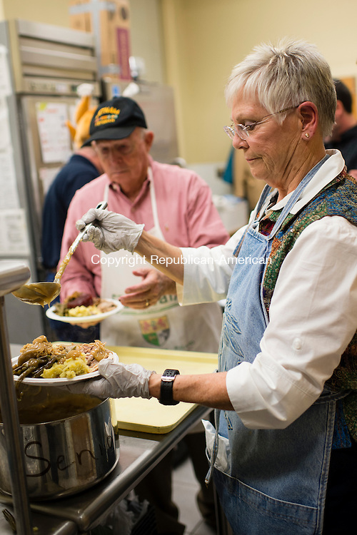 MIDDLEBURY, CT- 18 November 2015-111815EC02-  Sandy Regan scoops gravy while, behind her, Ray Sullivan stands ready to serve the prepared dinners to residents in the cafeteria at the Shepardson Community Center in Middlebury Wednesday night. The Lion's Club prepared meals for 200 people during its annual turkey dinner. Visitors received a traditional Thanksgiving meal with turkey, stuffing, mashed potatoes, green beans and pumpkin pie. Money raised benefits the Middlebury Family Services Emergency Fund and other community outreach programs. Erin Covey Republican-American