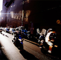 Vespas move down a street on a sunny afternoon in Florence, Italy in the summer of 2007.