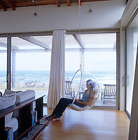 A girl sitting in an Eero Aarnio bubble chair suspended from the ceiling of the living room with a view of the ocean through the plate-glass windows