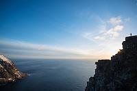 Silhouette of Landscape photographer on summit of Ryten, Moskenesoy, Lofoten Islands, Norway