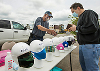 Terry Ackley (left) of Rogers sells a mask Thursday, May 14, 2020, to Brad Townzen of Bentonville in a vacant parking lot next to Harbor Freight Tools in Rogers. Ackley is selling hand sanitizer and a variety of masks including fabric masks made by his roommate, disposable surgical masks and commercial filter masks. He plans to be set up Friday as well. Go to nwaonline.com/200515Daily/ to see more photos.<br /> (NWA Democrat-Gazette/Ben Goff)