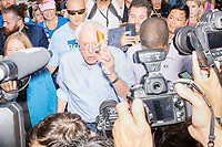 """Democratic presidential candidate Bernie Sanders eats a corndog at the Iowa State Fair in Des, Moines, Iowa, on Sun., Aug. 11, 2019. After taking a bite, Sanders said to the media, """"I'd like to make a major announcement. This is pretty good!"""""""
