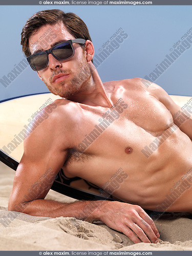 Portrait of a young man in sunglasses with a surfboard lying on the sand at the beach