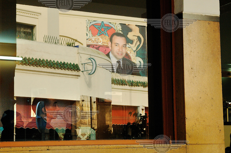 A man smokes a cigarette in a cafe in Habous, on a wall reflected in the cafe window is a photograph of king Mohammed VI, known as M6 in echo of a French TV channel.