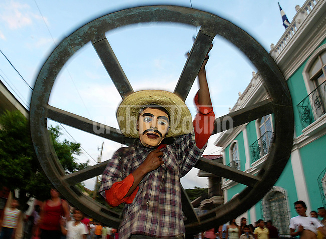 A masked man loads a wheel of a horse cart in the street paradeof Carnival in Masaya.,