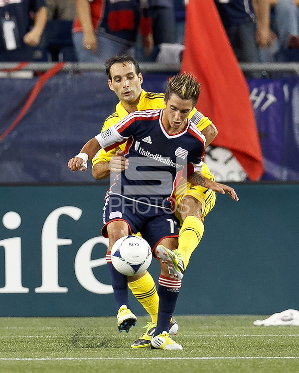 New England Revolution forward Diego Fagundez (14) dribbles as Columbus Crew defender Sebastian Miranda (21) defends. In a Major League Soccer (MLS) match, the New England Revolution defeated Columbus Crew, 2-0, at Gillette Stadium on September 5, 2012.