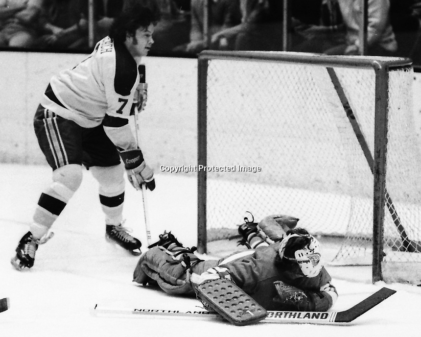 Seals Reggie Leach over Detroit Red Wings goalie Dennis DeJordy. (1974 photo/Ron Riesterer)