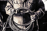 USA, Oregon, Enterprise, Cowboy Todd Nash holds his rope at the Snyder Ranch after a long day of moving cattle in the rain, Northeast Oregon