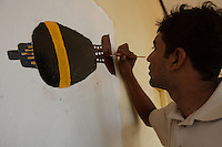 """A volunteer draws a mortar round on a wall to create awareness for undisposed explosives in his area in Trincomalee, Eastern Sri Lanka on Sunday October 08 2006..The Sri Lanka civil was is an ongoing conflict on the island nation of Sri Lanka Since the 1983 """"Black July""""  pogrom there has been on and off civil war, mostly between the government and the Liberation Tigers of Tamil Eelam, or the LTTE, who want to create an independent state of Tamil Eelam in the north east of the island. It is estimated that the war has left 65000 people dead since 1983 and caused great harm to the population and economy of the country. A cease fire was declared in 2001, but hostilities renewed in late 2005. Following escalation of violence         in July 2006, a senior rebel leader declared the ceasefire null and void, although both sides later reaffirmed their commitment to the ceasefire agreement. Hundreds of people, including military personnel, rebels, and Tamil, Sinhalese and muslim civilians have been killed in fighting this year. Thousands of civilians have been displaced, many coming from areas already stroke by the dec 2004 Tsunami.."""