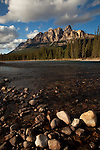 Castle Mountain seen with puffy cumulus clouds on a bright sunny day from the shore of the river.