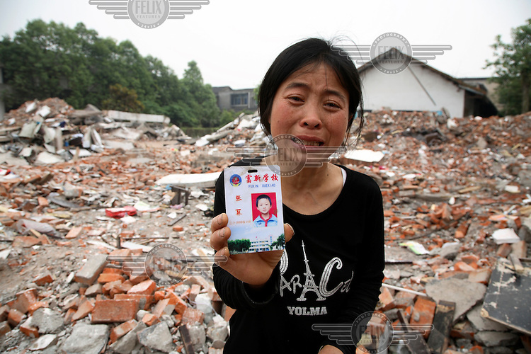 A grieving mother shows the school pass of her child, who died when his elementary school collapsed in Wufu. Over 200 students, all aged 10-13, and overwhelmingly from single-child families, were crushed when the building collapsed, yet most of the other buildings in Wufu sustained only minor damage. This has led angry and distraught parents to blame poor construction for the deaths of their children. The recent Sichuan earthquake of 12/05/2008 measured 8.0 on the Richter scale.