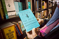 "A reader holds a copy  of ""Zen and the Art of Motorcycle Maintenance: An Inquiry into Values"" by Robert M. Pirsig in a bookstore in New York on Tuesday, April 25, 2017. Pirsig, the author of the book with a cult following, died in Maine on Monday at the age of 88. (© Richard B. Levine)"
