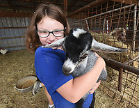 Aspen Boger, 10, hugs a one-month-old baby goat July 21 2020 at the Connie Boger family farm in the Hickory Creek community. Kids and adults can pet goats, pigs and a menagerie of farm animals at a petting zoo Boger operates on weekends. Her overall goal is to educate young people about agriculture.<br />(NWA Democrat-Gazette/Flip Putthoff)