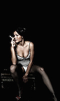 Model sitting on antique box with a cigaret in her right hand. Black backdrop