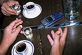 Belgrade, Yugoslavia. Table with coffee cups, mobile phone; glasses; shot glasses; hands from above.