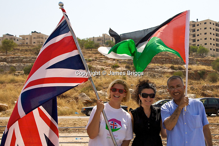 Ma'an reporter Razan Y. Salameh [Centre] alongside a representative of the British Consulate [Left] & Palestinian television journalist [Right] as the wave the Union Jack of Great Britain & the Palestinian national flag at a training session for young Palestinian women drivers in Ramallah on 12/06/2010. The event was organised by the British Consulate.