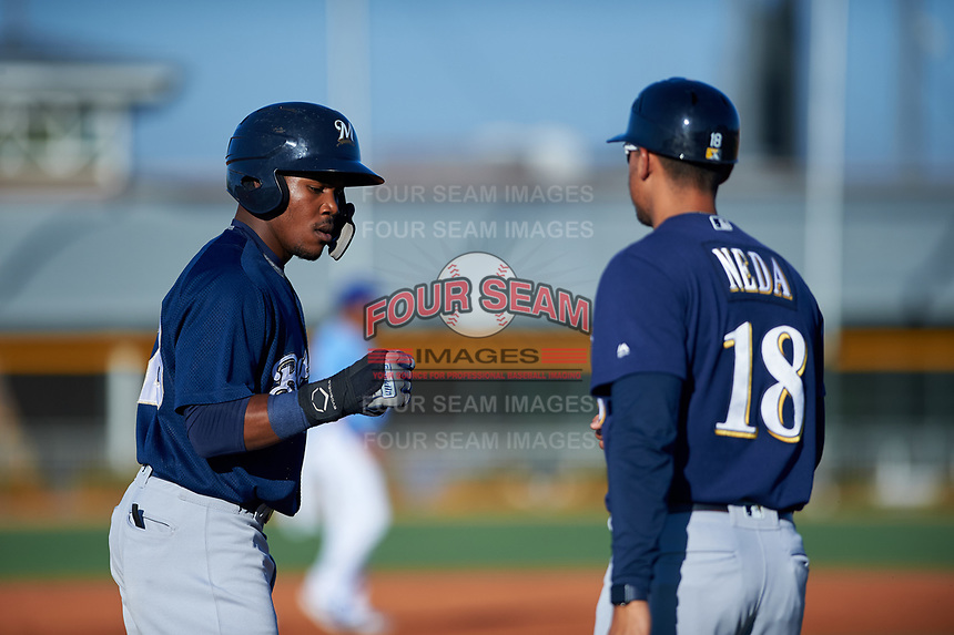 AZL Brewers Blue Arbert Cipion (23) is congratulated by manager Rafael Neda (18) after reaching third base during an Arizona League game against the AZL Royals at Surprise Stadium on June 18, 2019 in Surprise, Arizona. AZL Royals defeated AZL Brewers Blue 12-7. (Zachary Lucy/Four Seam Images)
