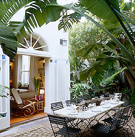 Lush plants overhang this cobbled courtyard where a dining table has been laid for lunch beyond the open double doors that lead into the living room