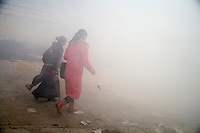 Girls walk through smoke caused by ceremonial prayer fires at the Labrang Monastery in Xiahe, Gansu, China.