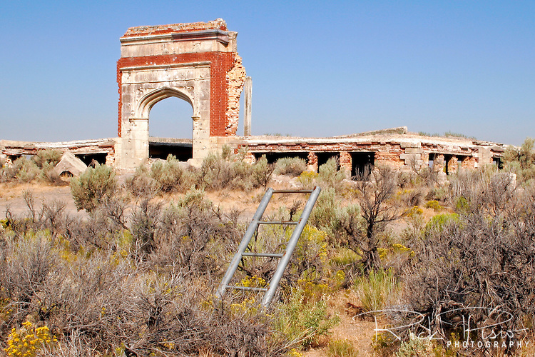 The remains of a piece of playground equipment sits in front of Lincoln High School ruins in the ghost town of Metropolis, Nevada. Metropolis was located northeast of Wells, Nevada, and was a planned town intended o be the center of a large farming district. Started when the Pacific Reclamation Company of New York bought 40,000 acres of land at the headwaters of the Humboldt River the anticipated population was 7,500. By 1911 a railroad spur, 3 story hotel, and high school were built. In 1912 the population began to increase and acreage was sold. In 1914 communities downstream from Metropolis filed suit over water rights against the dam that had been built across Bishop Creek leaving only enough water to irrigate 4,000 acres. By 1920 less than 100 residents remained. Lincoln High School opened in 1914 and taught its last class in 1947. The hotel burned down in 1936.