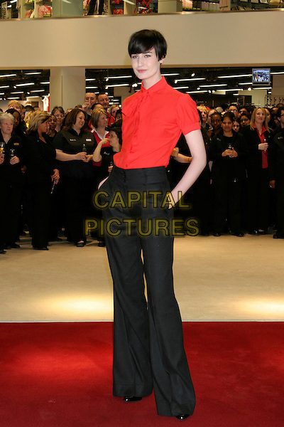 ERIN O'CONNOR.Opens the new M&S store at Colliers Wood, South London, England..May 1st, 2008.M & S Marks & Spencer full length red blouse tie black trousers hand in pocket.CAP/DS.©Dudley Smith/Capital Pictures