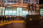 Supporters of both teams gathering in front of a statue in honour of Dennis Law, Bobby Charlton and George Best outside the main stand at Old Trafford before the Carling Cup semi-final second leg clash between Manchester United and Derby County. The visitors led one-nil from the first leg, however, United overturned this with a 4-2 victory to reach the final at Wembley.