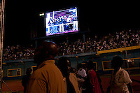 President Paul Kagame, his family and supporters are seen on a screen while they wait for the announcment of partial presidential election results at Amahoro stadium, Kigali, Rwanda. August 10 2010