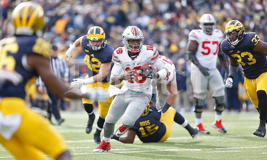 Ohio State Buckeyes quarterback J.T. Barrett (16) leaves a wake of Michigan players as he heads to the end zone at Michigan Stadium on November 28, 2015. (Chris Russell/Dispatch Photo)
