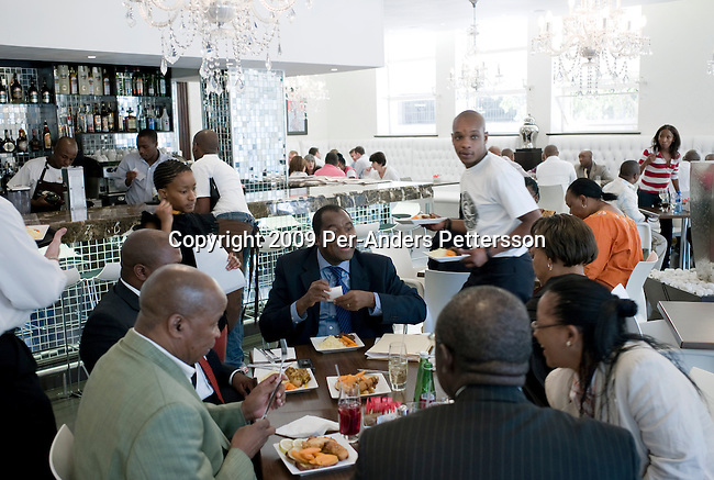 JOHANNESBURG, SOUTH AFRICA - MARCH 6:  Black up-market people eat lunch at Darkie restaurant on March 6, 2009, in central Johannesburg, South Africa. The newly opened trendy eatery is popular among black yuppies and black empowerment figures. Downtown Johannesburg was long a no go zone after dark but has seen an increase in security and businesses, restaurants and clubs moving in. Also, many deserted buildings have been converted into residential apartments. (Photo by: Per-Anders Pettersson/Getty Images)..