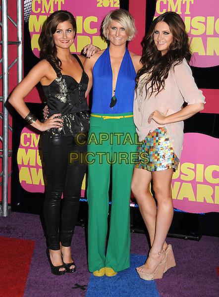 The McClymonts.2012 CMT Music Awards held at Bridgestone Arena, Nashville, Tennessee, USA..June 6th, 2012.full length black green blue pink skirt top trousers hand on hip.CAP/ADM/LF.©Laura Farr/AdMedia/Capital Pictures.