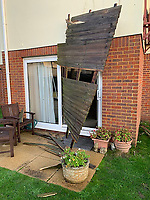 BNPS.co.uk (01202 558833)<br /> Pic: /BNPS.<br /> <br /> Fence embedded in a patio door.<br /> <br /> Homeowners are counting the cost today after a 'tornado' hit a south coast town overnight.<br /> <br /> Residents in Barton-on-Sea, Hants, were woken at 4am as the twister blasted its way through the town like an 'express train'. <br /> <br /> The strength of the winds of up to 80mph shook numerous houses, sending roof tiles smashing to the ground.<br />  <br /> A 30ft long brick wall collapsed under the strength of the gusts while fence panels were flung through the air.<br /> <br /> Part of a garden shed that had been picked up by the tornado smashed a hole through the windscreen of a car.